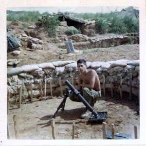 "Ron ""Baby Sanh"" Reyes posing in a mortar pit with a  60 mm mortar. Photo courtesy of Ron Reyes."