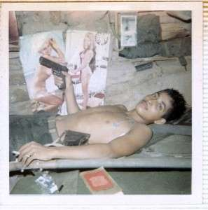 """Ron """"Baby Sanh"""" Reyes holding a M1911A1 .45 caliber pistol while relaxing in a bunker. Photo courtesy of Ron Reyes."""